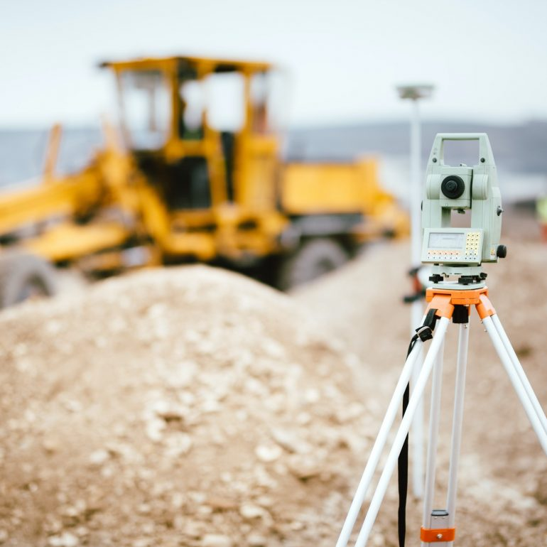 Surveyor equipment GPS system or theodolite outdoors at highway construction site.